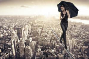 Femme funambule au dessus d'une ville.