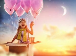 Enfant qui rit dans un carton qui s'envole emporté par des ballons.