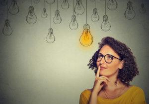 Femme pensive regarde une ampoule allumée.