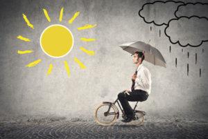 Homme à vélo va de la pluie vers le soleil.
